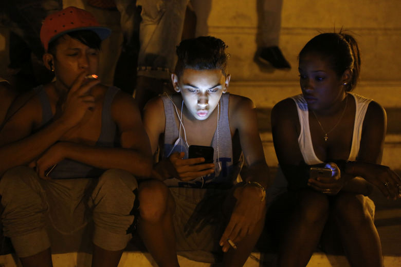 FILE – In this July 1, 2015 file photo, youths use a password protected wifi network coming from a five star hotel to surf the Internet on their smart phones in downtown Havana, Cuba. Cuba's government announced on Tuesday, Dec. 4, 2018 that its citizens will be offered full internet access on mobile phones starting Thursday, Dec. 6, becoming one of the last nations to do so. (AP Photo/Desmond Boylan, File)